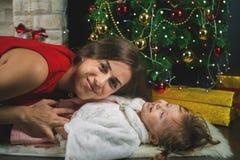 Grappige baby en mum dichtbij Kerstboom Nieuw jaar 2017 Royalty-vrije Stock Afbeeldingen