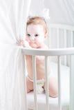 Grappige baby in luier het spelen in zijn voederbak royalty-vrije stock fotografie