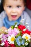 Grappige baby met bloemen Stock Foto's