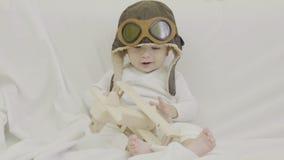 Grappige baby met vliegenier GLB het spelen met houten vliegtuigstuk speelgoed, gelukkig kind, het glimlachen conceptueel gezicht stock video