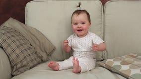 Grappige babyzitting op bank golvende handen en het glimlachen stock videobeelden