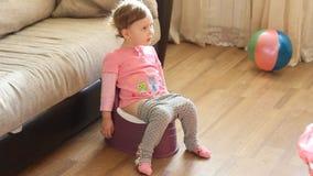 Grappige babyzitting op een pot stock footage