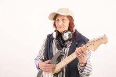 Grappige bejaarde dame die elektrische gitaar spelen Royalty-vrije Stock Foto's