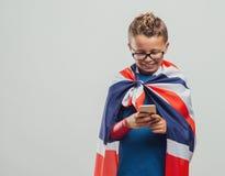 Grappige Britse superhero gebruikend een slimme telefoon royalty-vrije stock fotografie