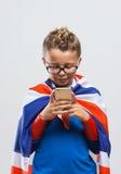 Grappige Britse superhero gebruikend een slimme telefoon stock foto
