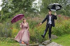 Grappige bruid en bruidegom in de herfst bij kleine kreek Royalty-vrije Stock Fotografie
