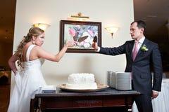 Grappige bruid en bruidegom dichtbij huwelijkscake Royalty-vrije Stock Fotografie