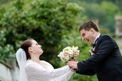 Grappige Bruid en Bruidegom met Huwelijksboeket Royalty-vrije Stock Foto's