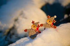 Grappige cijfers van herten op sneeuwpijnboomtakken Stock Foto