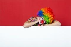 Grappige clown met band op lege raad Stock Afbeelding