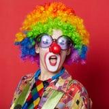Grappige clown met glazen op rood royalty-vrije stock fotografie