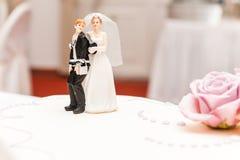 Grappige die bruid en bruidegom van suiker bovenop huwelijkscake wordt gemaakt stock foto