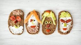 Grappige die gezichten van brood, boter, tonijn, worst, wortel worden gemaakt, paprik Stock Afbeeldingen
