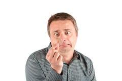 Grappige die mens door een gehoorapparaat wordt geschokt Geconcentreerd op het gehoorapparaat stock afbeelding
