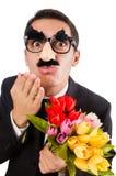 Grappige die mens met bloemen op wit wordt geïsoleerd Stock Fotografie