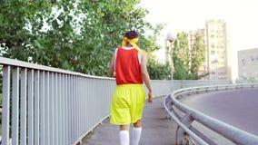 Grappige dunne kerel buitenissig in de gangen van sportenkleren vóór jogging stock videobeelden