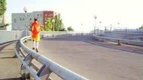 Grappige dunne kerel in een superherokostuum op een looppas op de brug binnen stock videobeelden