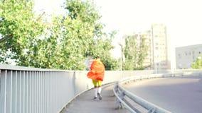 Grappige dunne kerel in een superherokostuum op een looppas op de brug binnen stock video