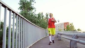 Grappige dunne kerel in sportenkleren het aanstoten stock video
