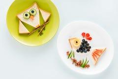 Grappige eigengemaakte sandwiches in vormen van vissen en uil op platen Stock Foto