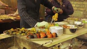 Grappige en dappere kok die maaltijd voorbereiden bij straatvoedsel fest, heer in een kostuum stock footage
