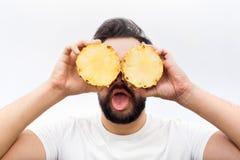 Grappige en positieve van de jonge mensentribune en dekking ogen met twee halfs van één ananas Ook toont hij tong op camera royalty-vrije stock fotografie