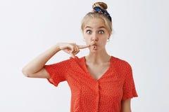 Grappige expressieve aantrekkelijke blonde vrouwelijke student in uitstekende rode stipblouse en hoofdband die mond in vissen vou royalty-vrije stock foto's