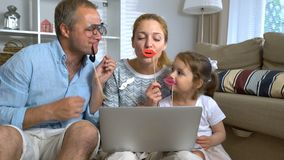 Grappige Familie het Babbelen Laptop Videovraag die de Carnaval-Toebehoren gebruiken stock video