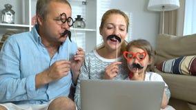 Grappige Familie het Babbelen Laptop Videovraag die de Carnaval-Toebehoren gebruiken stock videobeelden