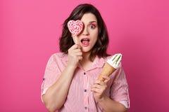 Grappige geïmponeerde mooie vrouw status geïsoleerd over roze achtergrond die in studio, haar oog en mond wijd met schok openen, stock foto's