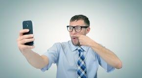 Grappige gebaarde zakenman die fotograferen op een smartphone royalty-vrije stock afbeeldingen