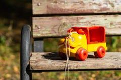 Grappige gele plastic stuk speelgoed auto op een parkbank stock afbeeldingen