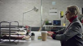 Grappige gelukkige jonge vrouw die terwijl het luisteren aan luide muziek in hoofdtelefoons die bij bureau met laptop zitten zing stock footage
