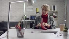 Grappige gelukkige jonge vrouw die terwijl het luisteren aan luide muziek in hoofdtelefoons die bij bureau met laptop zitten zing stock video