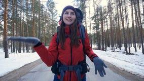 Grappige gelukkige toerist die pret hebben die op een de winterweg in bos lookung in camera dansen stock footage