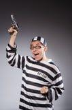 Grappige gevangene met vuurwapen op grijs royalty-vrije stock afbeelding