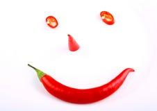 Grappige gezichts roodgloeiende peper op een plaat stock afbeelding