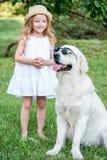 Grappige grote hond in zonnebril en leuk blondemeisje in witte kleding in openlucht in park Royalty-vrije Stock Afbeeldingen