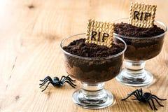 Grappige Halloween-chocolademousse met grafkoekje en spinnen op hout stock foto
