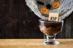 Grappige Halloween-chocolademousse met grafkoekje en spinnen op hout royalty-vrije stock afbeelding