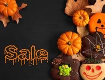 Grappige Halloween-peperkoekkoekjes op zwarte houten lijst De verkoop van Halloween stock afbeeldingen