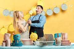 Grappige huisvrouw die haar echtgenoot in de keuken proberen te wassen royalty-vrije stock foto's
