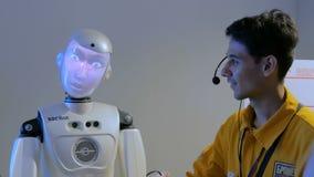 Grappige humanoidrobot met vertoningsgezicht die met gids, technologietentoonstelling spreken stock videobeelden