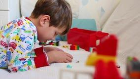 Grappige 5-6 jaar oude jong geitje speelspelen die in zijn bed in ochtend leggen Kind die smartphone gebruiken Leuke Kaukasische  stock video
