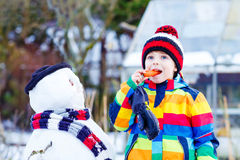 Grappige jong geitjejongen die in kleurrijke kleren een sneeuwman maken Stock Fotografie
