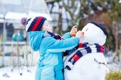 Grappige jong geitjejongen die in kleurrijke kleren een sneeuwman maken, in openlucht Stock Afbeeldingen