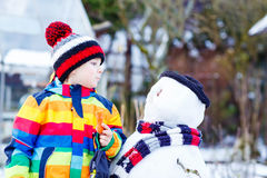 Grappige jong geitjejongen die in kleurrijke kleren een sneeuwman maken, in openlucht Stock Afbeelding
