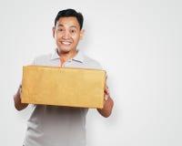 Grappige Jonge Aziatische Koerier Guy Giving Package Box stock afbeelding