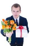 Grappige jonge die mens met bos van bloemen en giftdoos op w wordt geïsoleerd Stock Foto's