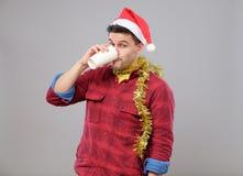 Grappige jonge gedronken mens die Kerstmanhoed dragen die een document kop houden royalty-vrije stock fotografie